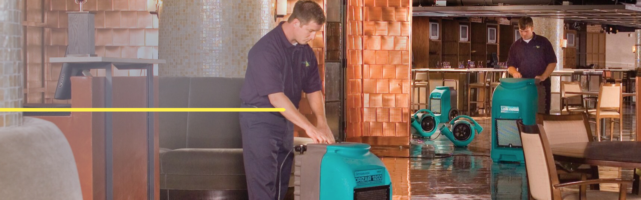 servicemaster technicians cleaning water in restaurant